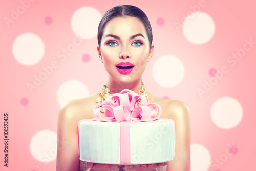 Fashion model girl holding beautiful party or birthday cake on pink background