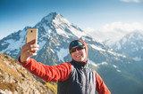 Happy woman hiker on the top of mountain making selfie