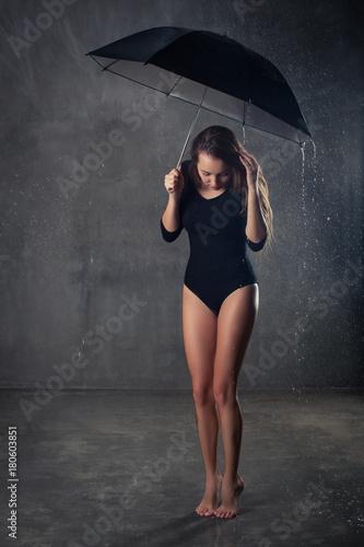Juliste beautiful girl photo under the umbrella during rain barefoot on a dark backgroun