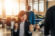 Smiling woman receives the keys to a new car from a sales manager.