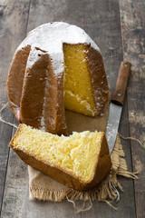 Pandoro Christmas cake with sugar on wooden table