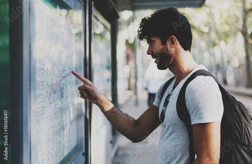 Young bearded traveler man searching the route on a public transportation system map in unknown city. Handsome guy with backpack pointing finger on train timetable on a railway station.