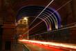 Most Tower Bridge w Londynie, nocą, kolorowo podświetlony, smugi świetlne od poruszających się pojazdów, długi czas naświetlania - 180621297