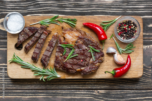 Fotobehang Steakhouse Beef steak with herbs and spices on wooden background