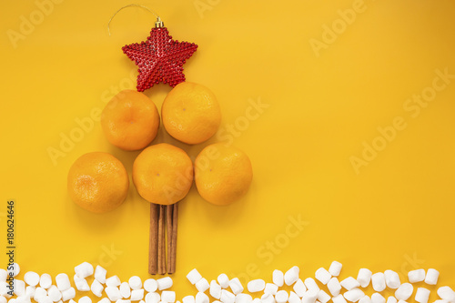 Christmas tree make of tangerines, cinnamon, red star, marshmallow on an orange background, top view. happy new year 2018. copy space - 180624646