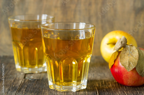 Fotobehang Sap Apple juice in glasses and fresh apples on a wooden background. Rustic style.