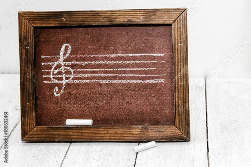Fototapeta Music figure and treble clef drawn in chalk on a school board. The theory of music. Musical education