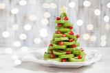 Healthy dessert idea for kids party - funny edible kiwi pomegranate Christmas tree - 180634800