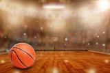 Fototapeta Sport - Fictitious basketball arena with ball on court and copy space. Camera flashes and lens flare special lighting effect on defocused background. © ronniechua
