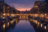 Purple cloudy sky, reflections in the water, boats and cosy-lighted streets during a twilight blue hour sunset, Amsterdam, Netherlands