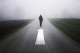 Man walk alone on foggy road with straight up arrow sign painted on the road. - 180644074