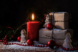 christmas gift boxes and a burning candle in the snow, decorated with red ornaments, fir branches and small wooden toy trees, dark rustic background with copy space - 180645011