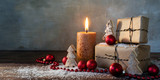 two gift boxes and a burning candle, red christmas baubles and small wooden toy trees in some snow on rustic wood, vintage background with large copy space, panorama format - 180645097