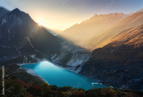Mountain valley and lake with turquoise water at sunrise in Nepal. Majestical landscape with high mountains, lake, lightened hills, rocks, sun with yellow light and sky. Bright sunny morning. Travel © den-belitsky