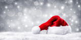 Santa Hat On Snow And Silver Shiny Background - 180653464