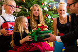 Parents and children with presents on Christmas day  - 180654227