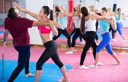 Wall mural Group of female are doing box exercises with instructor