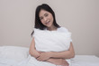 Smiling young woman hugging with pillow sitting on bed at home in bedroom.