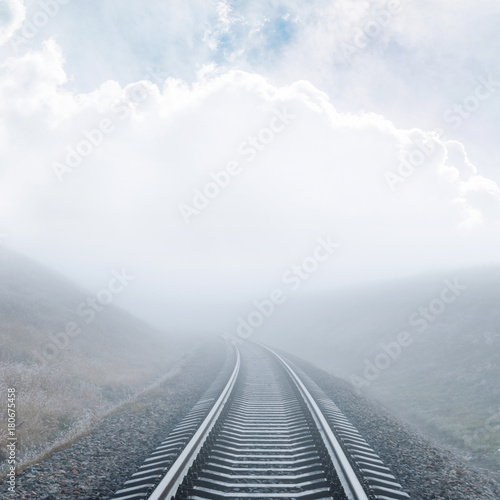 railway closeup goes to horizon in fog under cloudy sky - 180675458