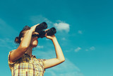 Beautiful Young Girl Looking Through Binoculars On Blue Sky Background. Travel Holidays Journey Concept - 180681637