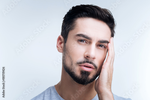 Unpleasant headache. Ill unhappy young man standing against the blue background and touching his head while having a terrible headache