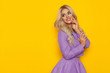 Beuatiful Blond Woman In Violet Costume Is Smiling And Looking At Yellow Copy Space