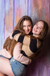 Half length of two attractive teenage girls hugging over the painted wall. Wearing pullovers and jeans shorts.