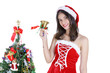 Christmas concept : Beautiful young Asian woman in Santa Claus costume holding handbell with decorated Christmas tree isolated on white background