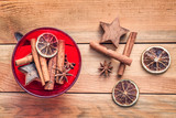 Bowl of Christmas spices with dried orange and cinnamon on wooden background, vintage christmas decor - 180726053