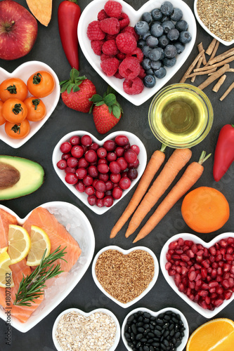 Health food for a healthy heart with berry fruit, vegetables, seeds, pulses, cereal and olive oil on slate background. High in omega 3 fatty acid and antioxidants. © marilyn barbone