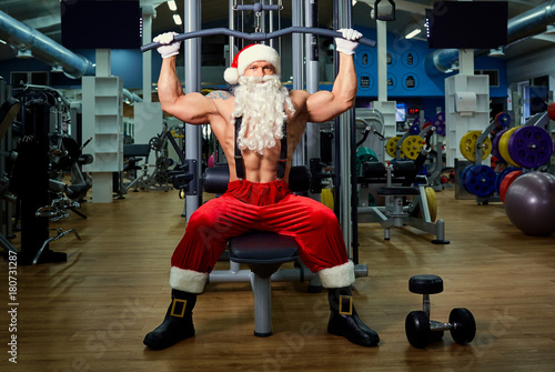 Wall mural Santa Claus Bodybuilder training at the gym on Christmas Day.