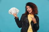 Pleased african woman in leather jacket holding money - 180738074