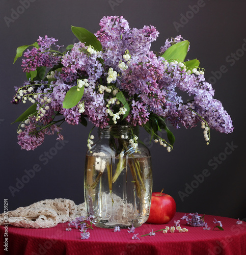 Fotobehang Lelietjes van dalen Spring bouquet of lilies of the valley and a garden of lilacs