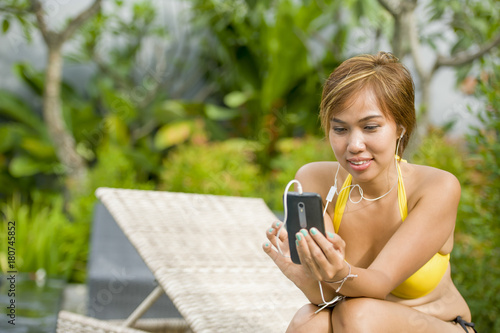 Poster young attractive and happy Asian woman using social media internet app on mobile