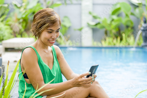 young attractive and happy Asian woman using social media internet app on mobile phone relaxed at resort swimming pool