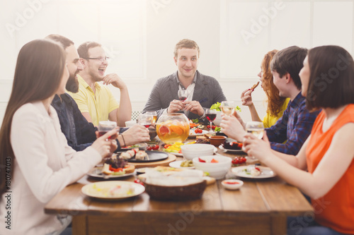 Group of happy people drink wine at festive table dinner party - 180747013