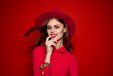 woman in hat with brown hair on red background - 180748223