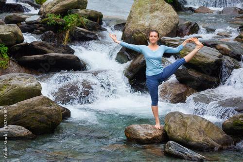 Wall mural Woman doing Ashtanga Vinyasa Yoga asana outdoors at waterfall