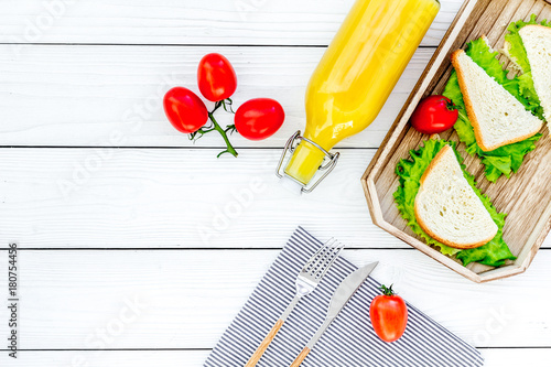 Fototapeta Sandwiches with lettuce and tomato for picnic on tablecloth on white wooden table background top view copyspace