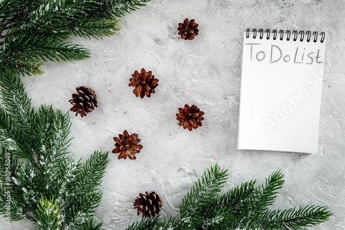 To do list for winter shopping at notebook near spruce branch and pinecones on grey stone background top view