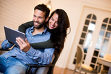 Young couple sitting in the living room and using tablet