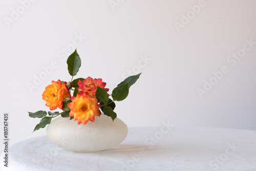 Red, orange and yellow roses in small glass vase on white tablecloth against white background