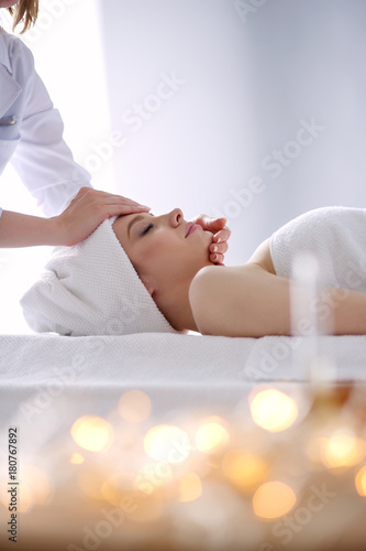 Young woman lying on a massage table,relaxing with eyes closed. Woman. Spa salon - 180767892