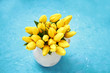 Yellow tulips in vase on blue background. Bouquet. Copy space, top view.