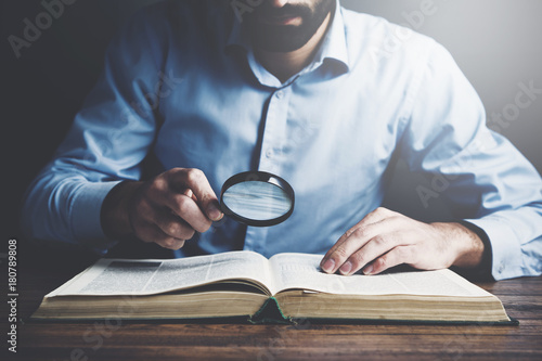 man hand magnifier reading book
