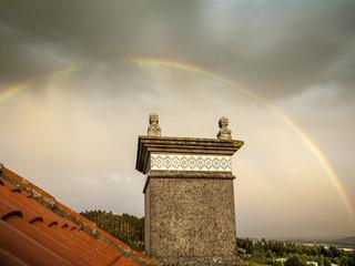 Arco iris completo sobre una chimenea bajo un cielo tormentoso