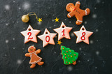 Inscription 2018 year from icing gingerbread cookies with 2018 numbers, gingerbread man and girl, fir tree on a black background. Festive concept. Toned. - 180808497