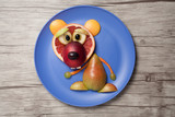Bear made of fruits on plate and table