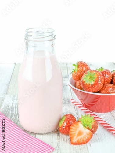 Foto op Aluminium Milkshake A bottle of strawberry yogurt milkshakes on a wooden table with fresh fruit and copy space
