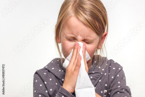 Poster Ein Mädchen schnäuzt in ein weißes Taschentuch